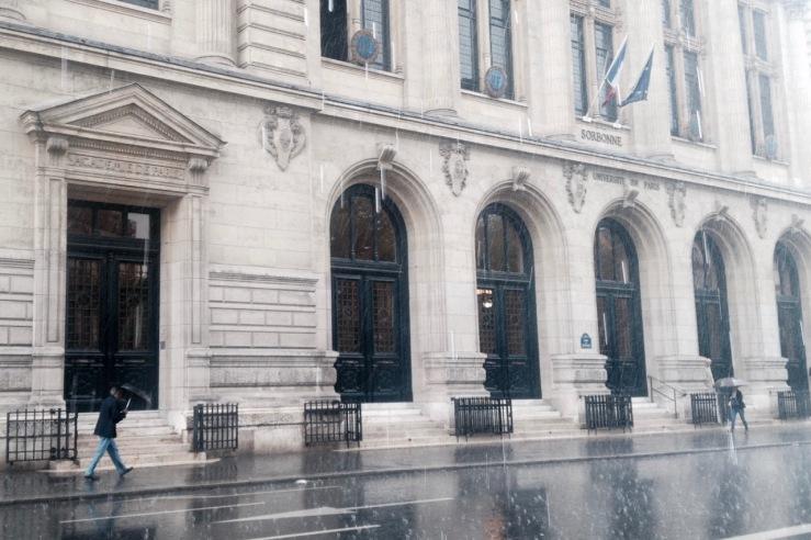 Straat met een man die in de regen loopt in Parijs